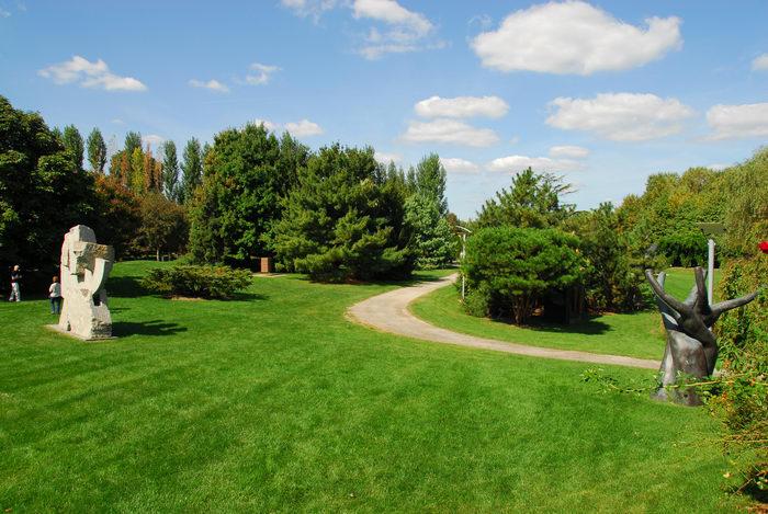 Sculptures, blue sky, grass, trees