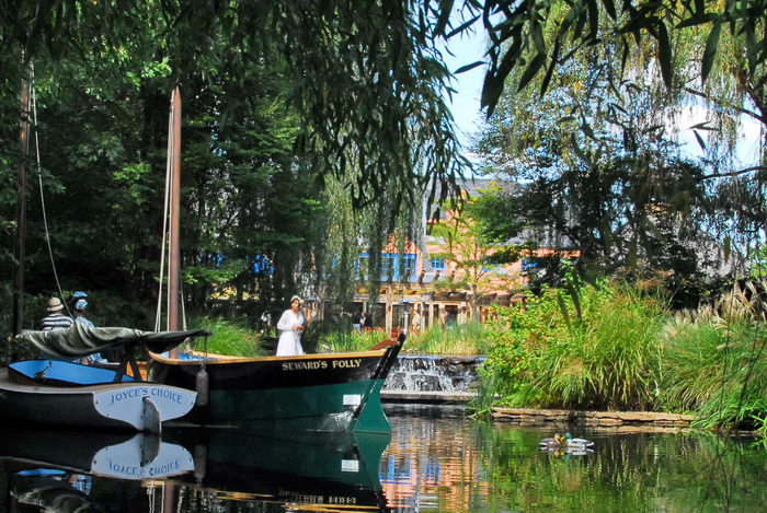 Sculptures, boats, trees, waterm reflection