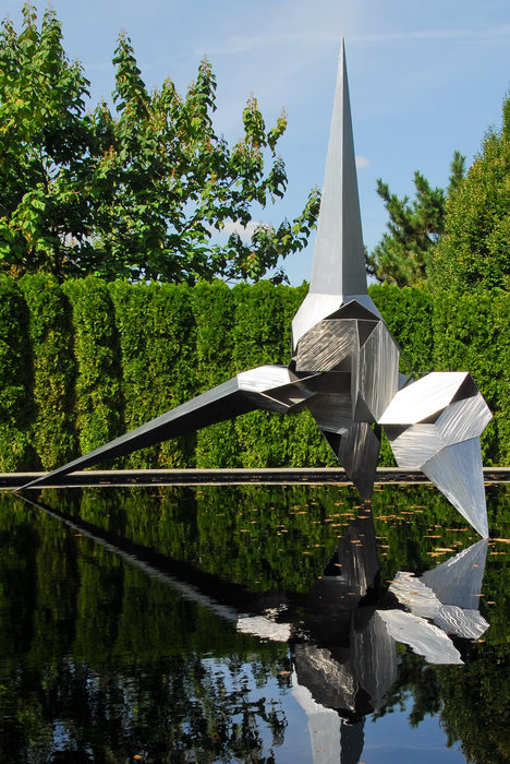 Sculptures, blue sky, metal building, reflection, trees, water