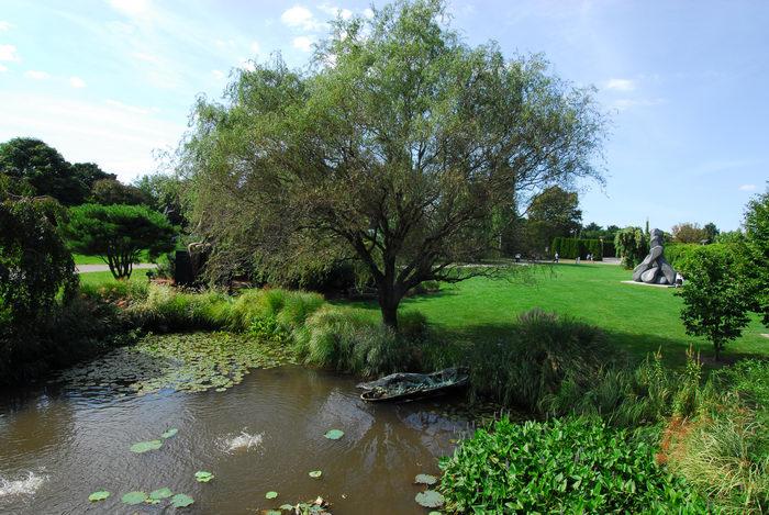 blue sky, grass, pond, sculpture, trees