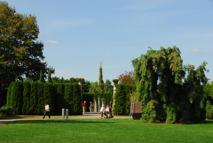 Sculptures, blue sky, grass, people, trees