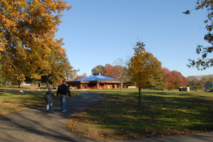 blue sky, building, fall colors, field, grass, open areas, path, shadow, trees, walkway
