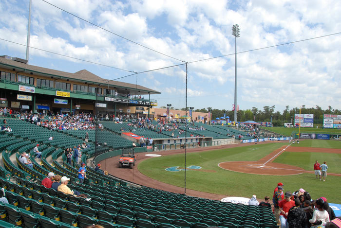 blue sky, clouds, grass, lights, net, people, seats, signs, stadium