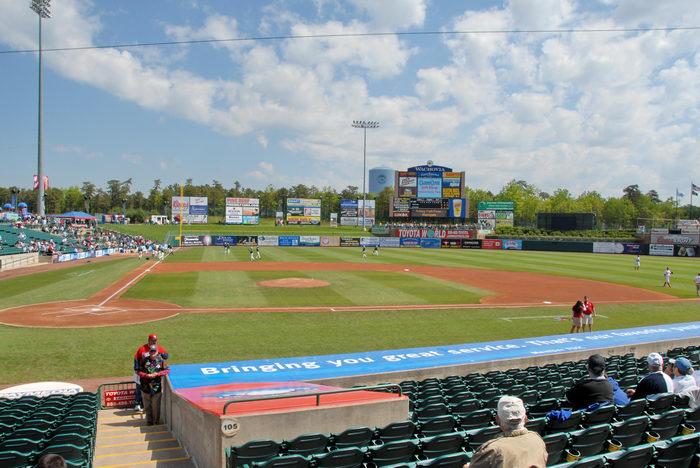 baseball diamond, bases, blue sky, clouds, grass, people, seats, signs, stadium