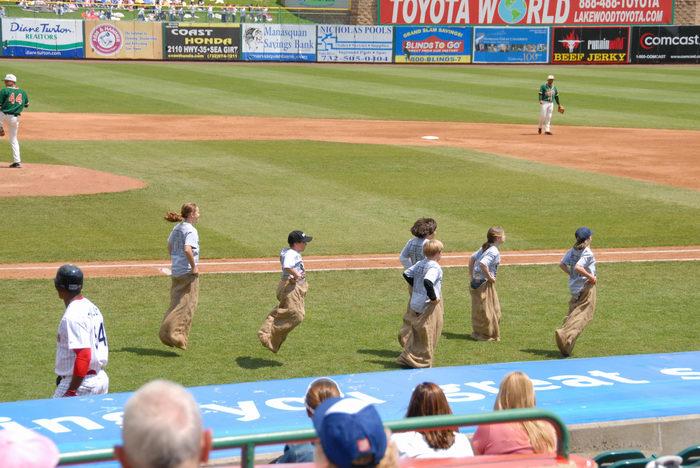 baseball player, grass, potato sack race, sign
