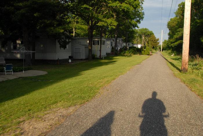 bike path, blue sky, grass, telephone pole, trailers, trees