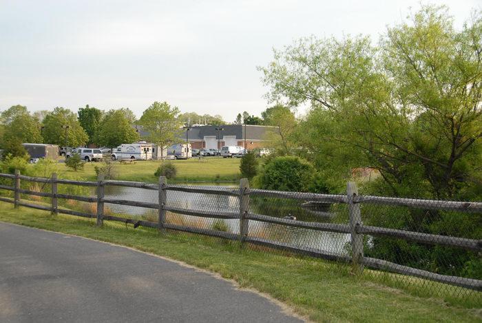 bike path, emergency vehicle, fence, grass, pond, trees, water