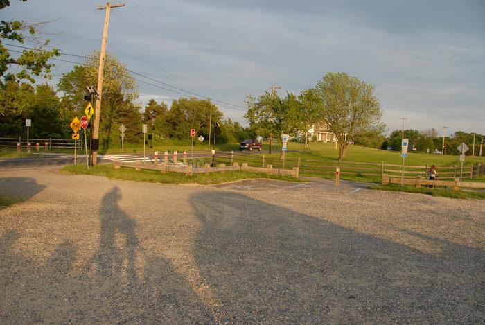bike path, dirt, fence, grass, parking lot, trees