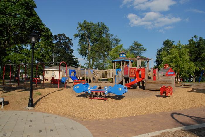 blue sky, play area, playground, light pole, trees, path