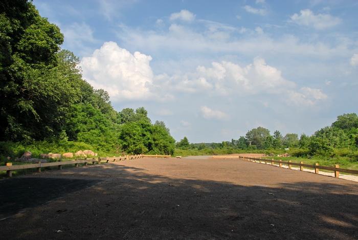blue sky, parking lot, dirt parking, trees, clouds, railing