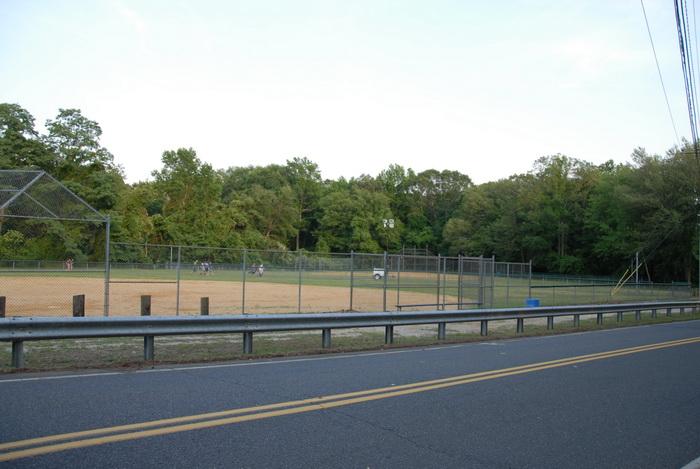 baseball diamond, baseball field, fence, grass, trees, road