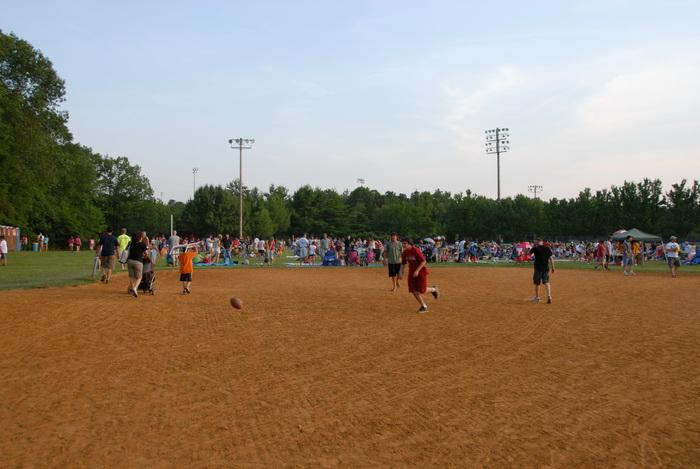 baseball diamond, baseball field, festival, grass, people, trees