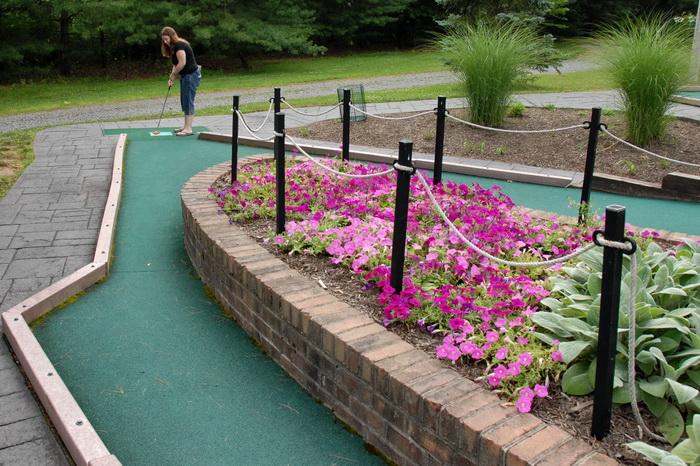 brick, flowers, grass, minigolf, obstacle, rope, trees, golf ball, golf green