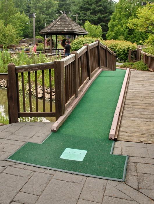 gazebo, minigolf, golf green, bridge, fence, people, bushes, trees