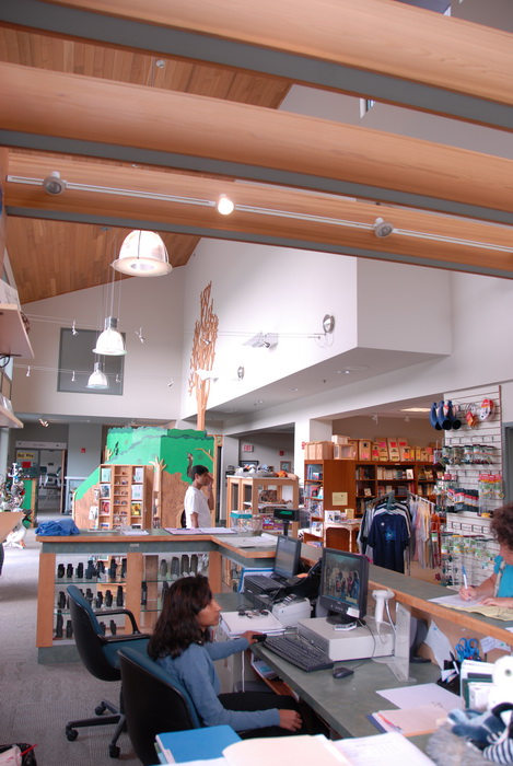 nature center, wood ceiling, beamed ceiling, lights, books, desk, computer, chairs, people