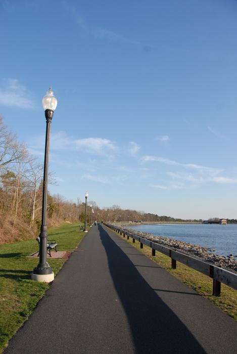 grass, light pole, lights, path, paved path, railing, rocks, trees, water