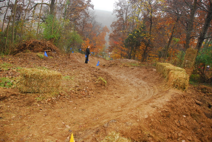 downhill mountain bike track, flags, hay bales, mud, signs, trees, woods, Jackie