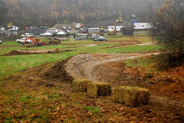 downhill mountain bike track, hay bales, mud, burms, turns, grass, cars, parking lot