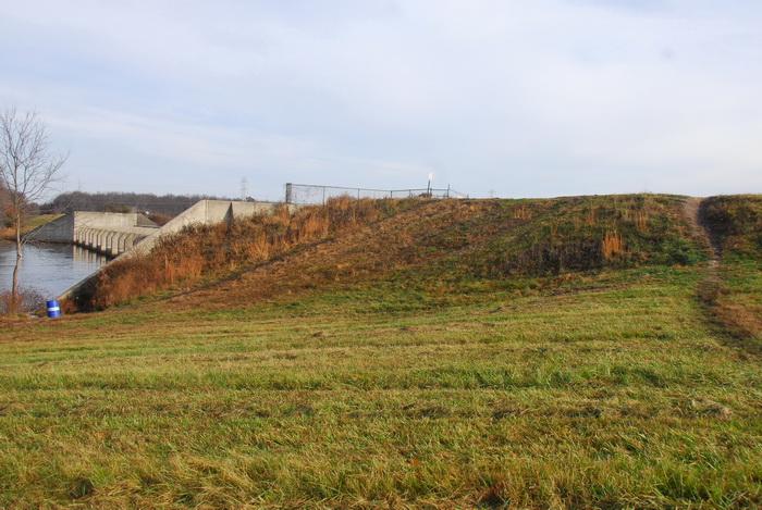 bike path, dam, dirt path, fence, field, grass, hill, trail, water