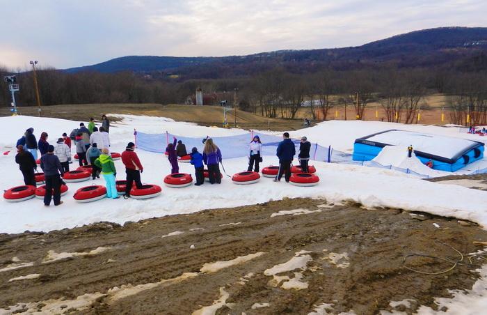 crowd, people, tubes, tubing, large jump, snow, ramp